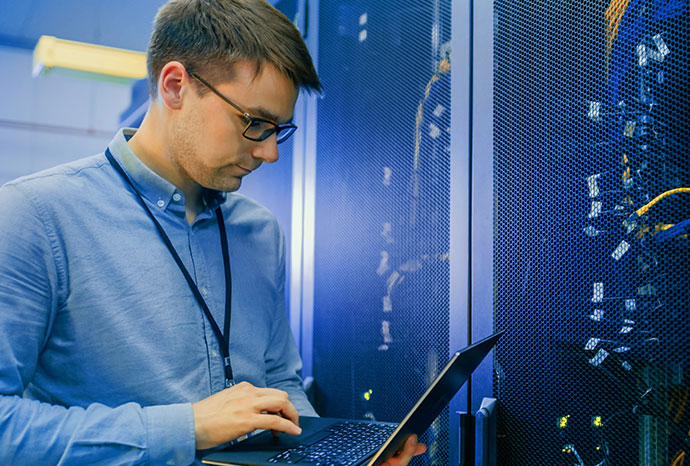 Data Center IT Engineer stands before server rack doing routine maintenance and diagnostics using a laptop